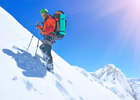 summits: Mountaineer reaches the top of a snowy mountain Stock Photo