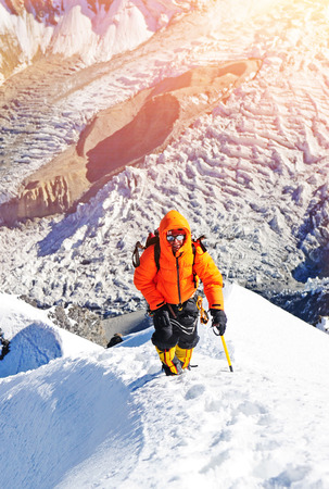 snowy mountains: Mountaineer reaches the top of a snowy mountain Stock Photo