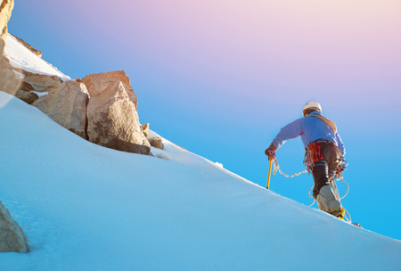 mountain valley: Mountaineer reaches the top of a snowy mountain Stock Photo