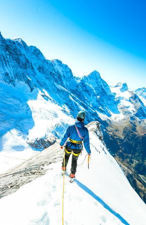 balances: Alpine climber balances on the ice snowfield. Extreme sport concept Stock Photo