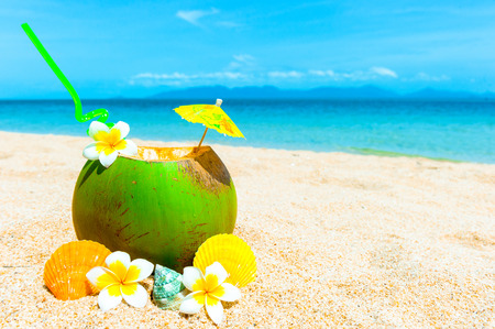 exotic food: Tropical fresh coconut cocktail on white beach. Vacation concept
