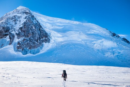 A climber reaching the summit of the mountain.