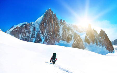 summits: A climber reaching the summit. Extreme sport concept