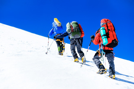 Group of climbers reaching the summit. Extreme sport concept Stock Photo