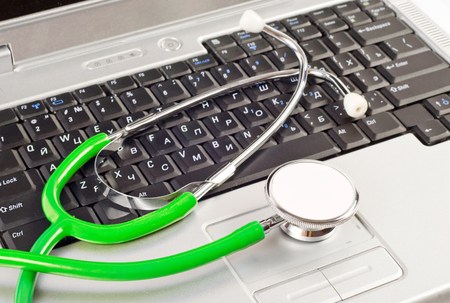 Stethoscope over a computer keyboard Stock Photo