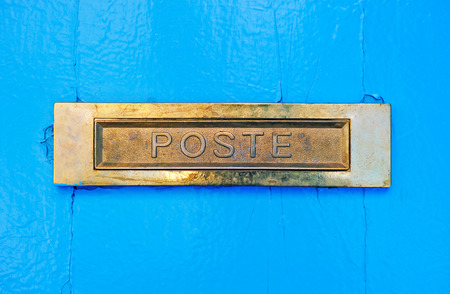 A metallic letterbox in a blue wooden door Stock Photo