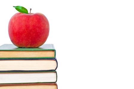 School and Education. Books tower with apple isolated on white