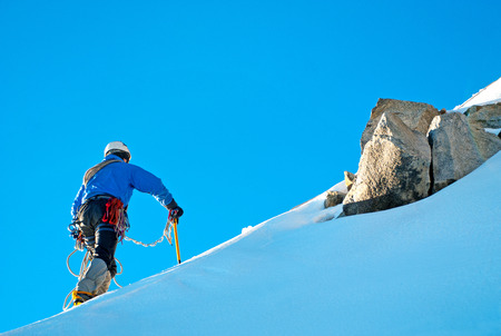 steep: Alpine climber balances on the ice snowfield