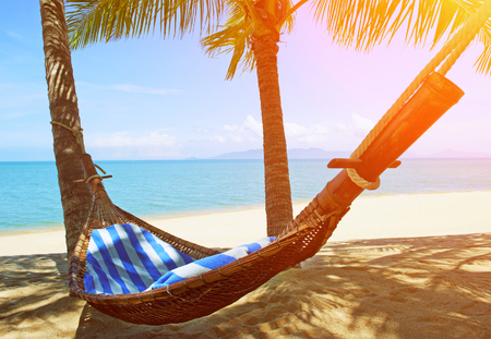 Beautiful beach. Hammock between two palm trees on the beach. Holiday and vacation concept. Tropical beach. Beautiful tropical island. Stock Photo