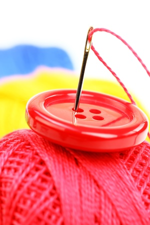 Colored thread, needles and buttons on a white background  photo