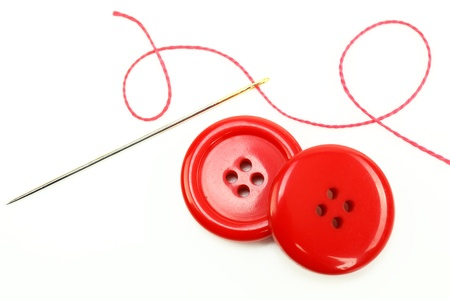 hilo rojo: Colored thread, needles and buttons on a white background  Foto de archivo