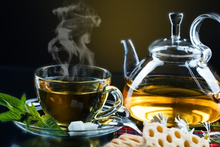 hot tea: Cup with green tea and green leaves