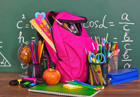 school bag: Volver a la pizarra de la escuela con pencilbox y material escolar en la mesa Foto de archivo