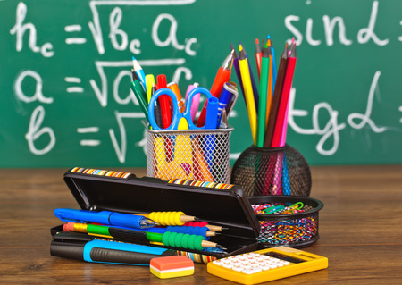 Back to school blackboard with pencilbox and school equipment on table photo