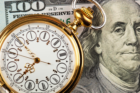 action fund: Old clock on a background of dollars