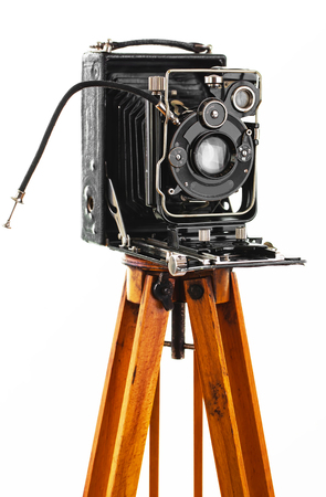 Old camera on white background on a tripod close-up