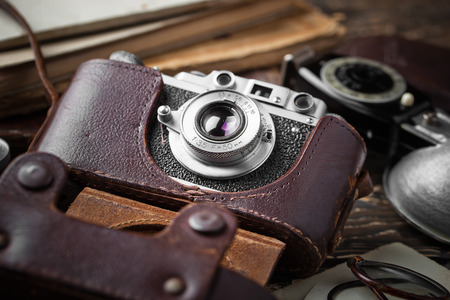 Old camera on a desk on an old background, closeup Stock Photo