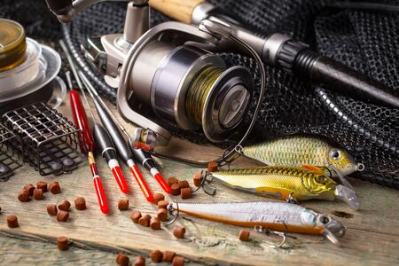 Fishing rods and spinnings in the composition with accessories for fishing on the old background on the table Standard-Bild