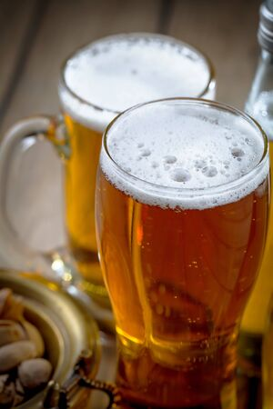 Light beer in a glass on a table in composition with accessories on an old background Foto de archivo