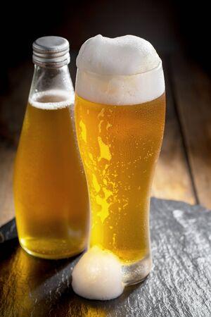 Bière légère dans un verre sur une table en composition avec accessoires sur fond ancien