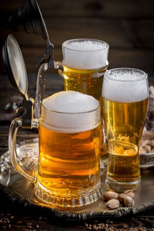 Light beer in a glass on a table in composition with accessories on an old background Imagens