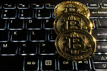 Three bitcoins on a computer keyboard. Фото со стока