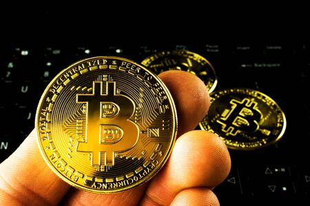 Bitcoin in the hands of a man. Three bitcoins on a computer keyboard.