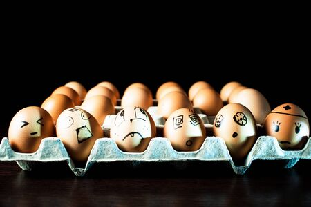 Emotional chicken eggs in a tray. Interesting grimaces drawn on chicken eggs.