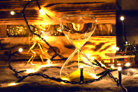 Hourglass on the background of a box with toys for the Christmas tree. For the moment, before Christmas.