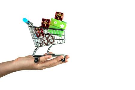 A girl holds a small shopping cart with Christmas gifts on her palm Stock fotó