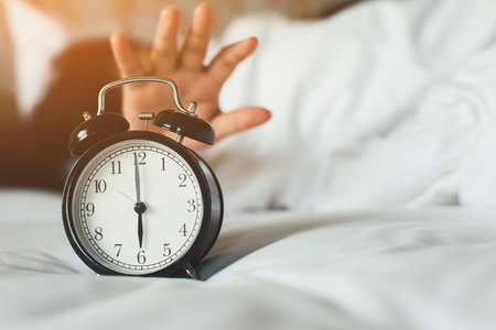 The womans hand under the blanket reaches out for the alarm clock. Alarm clock that reminds the morning.