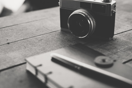 Notebook with pen And Vintage camera are placed on wooden boards. 스톡 콘텐츠