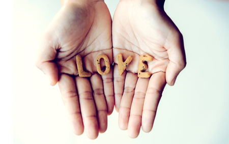 Cookies are letters that are arranged in love. The word love is in the hand. Valentine day
