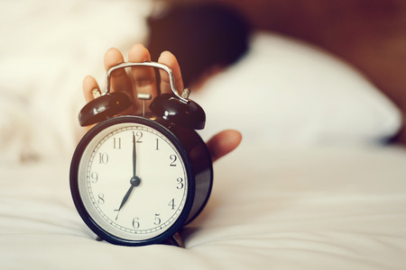 The woman's hand under the blanket reaches out for the alarm clock. Alarm clock that reminds the morning.