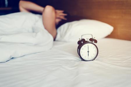 담요 아래에있는 여자의 손이 알람 시계에 손을 뻗습니다. 아침을 상기시키는 알람 시계. 스톡 콘텐츠 - 94193357