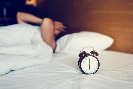 The woman's hand under the blanket reaches out for the alarm clock.
