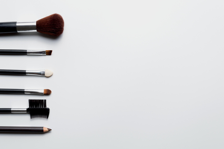 Cosmetic brush placed on a white background, top view.
