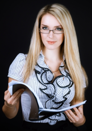 smart girl: smiling business woman in glasses holding folder on black  Stock Photo