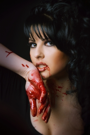 beauty vampire girl with blood on face on black background photo