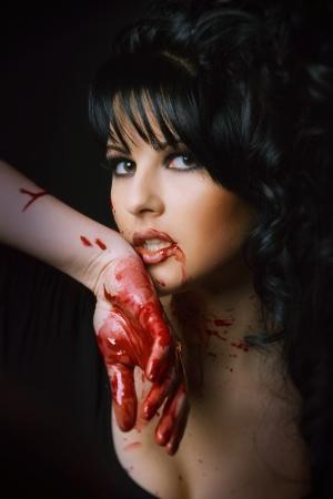 schoonheid vampier meisje met bloed op het gezicht op zwarte achtergrond