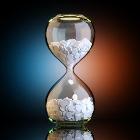 sand clock: Orologio di sabbia con le pillole in nero studio con retroilluminazione Artistico Archivio Fotografico