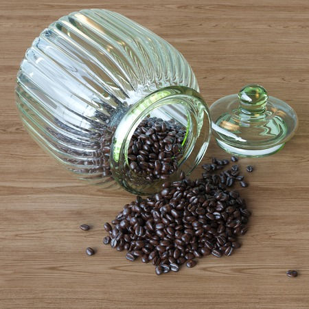 Coffee beans spilling out vintage glass jar on wooden surface photo