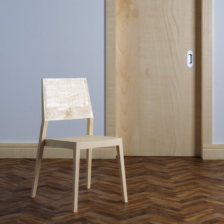 Wooden chair near the door in room interior with parquet photo