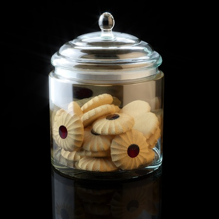 glass jar: Glass jar full of chocolate cookies on black background