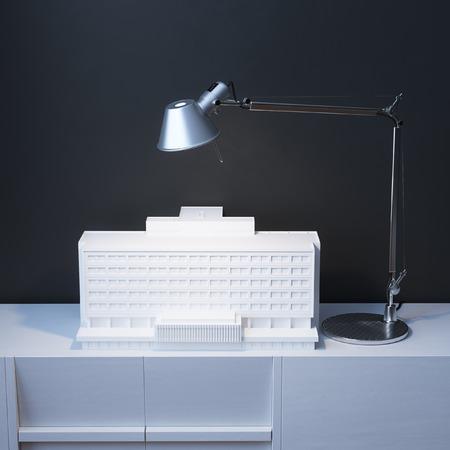 desk lamp: Model Of Building Under The Lamp On The Desk