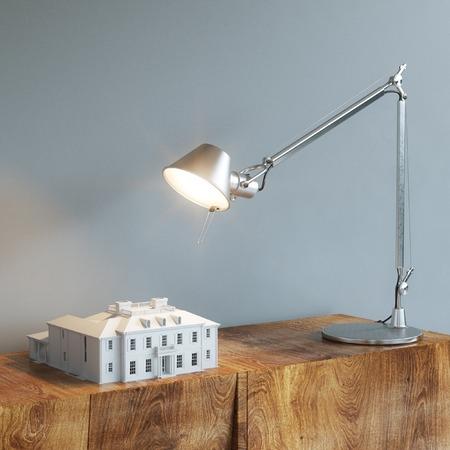 3D-model van het gebouw onder het bureau lamp licht op houten tafel