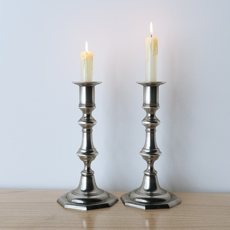 Retro candelabra with burning candles on wooden surface