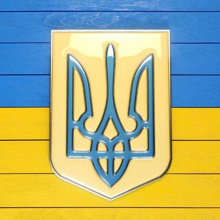 rada: Metal ukrainian trident on wooden yellowblue background Stock Photo