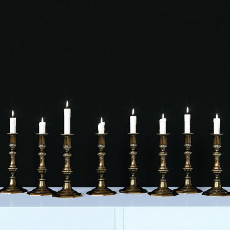 Burning candles in a vintage golden candlesticks. 3d render