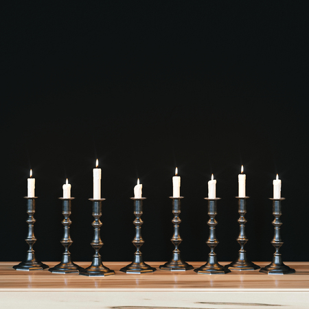 Several vintage candlesticks on wooden nightstand against the background of black wall. Candles burn. 3d render